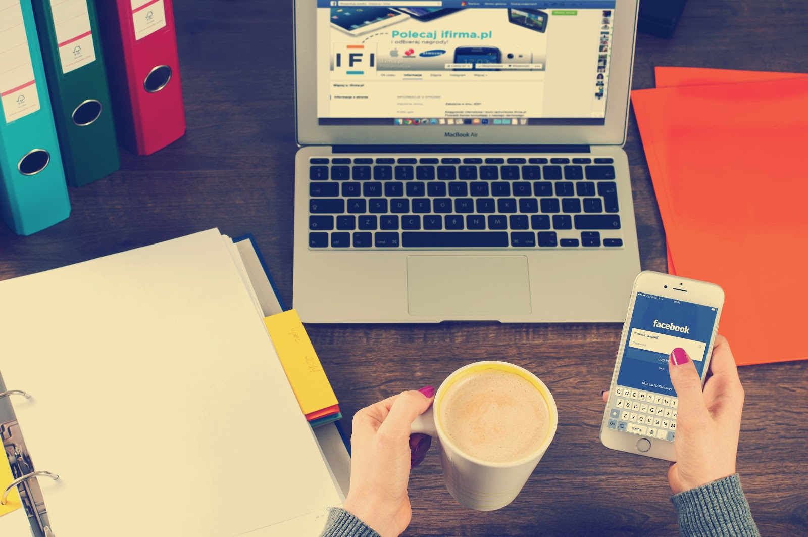photographie d'une femme qui tient un chocolat chaud et son portable avec l'application facebook d'ouverte.