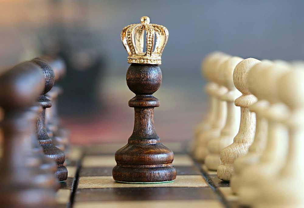 photographie d'un échiquier, un pion a une couronne sur la tête