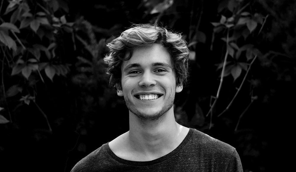 Photographie en noir et blanc d'un homme qui sourit face à la caméra.