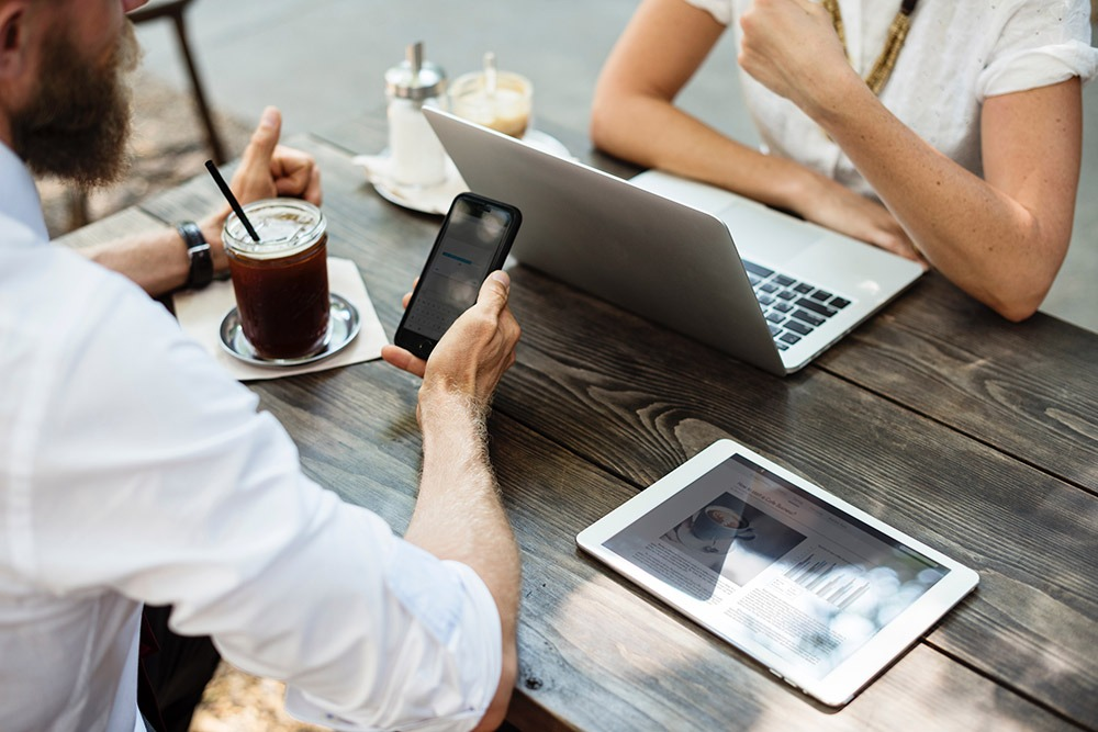 Photographie d'un homme tenant un portable, une tablette est aussi posée sur la table et une femme est sur son ordinateur en face de lui