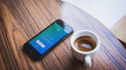 photographie d'un portable ouvert sur l'application twitter avec un café